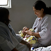 A woman with her newborn infant at the Ayacucho Regional Hospital...The Ayacucho Regional hospital is the largest government hospital in the region - serving approximately 580,000 people. The hospital is committed to respecting the practices of the indigenous community within the region by supporting their traditional birthing practices. Doing so encourages more indigenous women to give birth in the hospital while maintaining their cultural practices, but in a safer environment thereby reducing maternal mortality. Vertical birthing, for example, is common for the Qechua community. Women believe that their feet should be planted on the ground when they are giving birth and their partners need to be involved in the process by typically standing behind them and pushing on the women's belly while she delivers the baby.