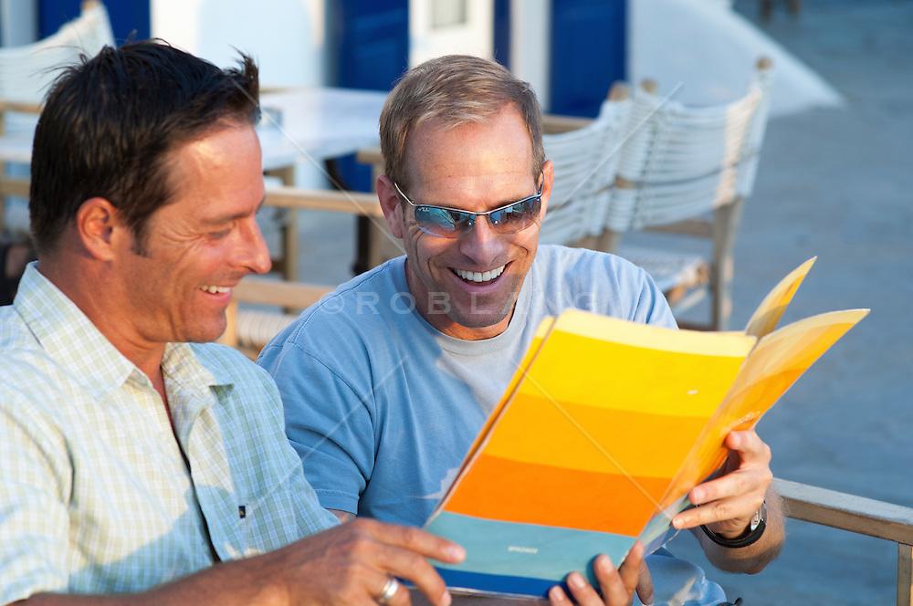two men looking at a menu at a cafe