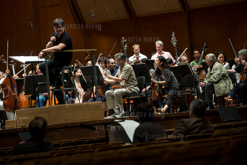 June 3, 2014 - New York, NY : As part of the New York Philharmonic Biennial, the orchestra solicited pieces from little-known composers and will choose three to play. Pictured here, Philharmonic Music Director Alan Gilbert, on podium (on stage with the New York Philharmonic) confers with composer Max Grafe, who is visible at foreground center, working with mentor composer Robert Beaser, far right, on Tuesday. CREDIT: Karsten Moran for The New York Times