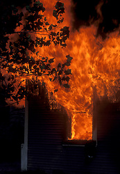 Stock photo of a house fire shooting flames from the windows