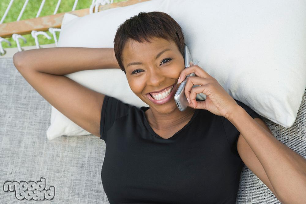 Woman using mobile phone in hammock, portrait