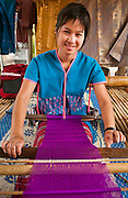 Young woman weaving cloth on loom; Patara Elephant Farm, Chiang Mai Province, Thailand.