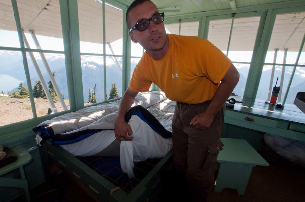 Dan the Fire Lookout Shows Off Ropes Under Mattress to Ward Off Electrical Storm Hazard, Desolation Peak, North Cascades Natonal Park, Washington, US