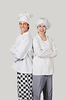 Portrait of young man and woman in chef's uniform with arms crossed against gray background