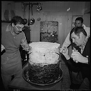 Die Osterspend von Ferden. Traditional Easter Offering in Ferden.Das Dorf Ferden am Eingang zum Lötschental ist jeweils am Ostermontag nach jahrhundertaltem Brauch Gastgeber der traditionellen Spend. Bei diesem Brauch wird ein während Monaten gelagerter Ziger-käse an die Talbevölkerung verteilt, zusammen mit einem Stück Brot und einem Glas Wein. Die Spende geht auf Versprechen aus dem Mittelalter zurück. Zur Zigerherstellung wird die Milch der drei Alpen Kummen, Resti und Faldum, die vom Abend des 22. Juni bis zum Morgen des 24. Juni anfällt, genommen. Die gesammelte Rohmilch wird zu kleinen, weichen Käselaiben verkäst und anschliessend in den Gemeindekeller von Ferden gebracht. Dort werden die Käselaibe zerkleinert, in die Stampftröge geleert und mit dem Stampfholz so lange zerstampft, bis ein feiner Brei entsteht. Sodann wird Salz in den Brei eingeknetet..Nun wird die Masse in spezielle Rindenfässer, genannt Rümpfe, eingefüllt.© Romano P. Riedo