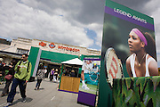 Day 2 of the annual lawn tennis championships and spectators mingle with locals near a large billboard of Ladies champion, Serena Williams seen outside the mainline and underground (subway) station in the south London suburb. The Wimbledon Championships, the oldest tennis tournament in the world, have been held at the nearby All England Club since 1877.