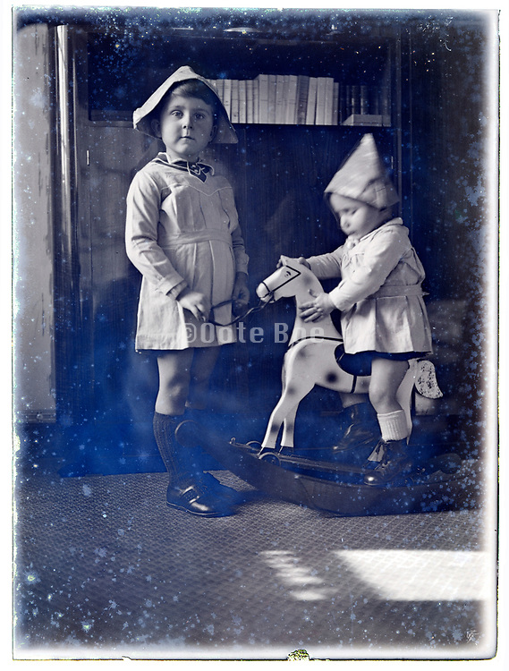 toddler sitting on a rocking horse and little child vintage 1920s