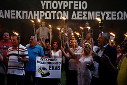 June 15, 2017 - Athens, Greece - Workers at public hospitals hold lit torches standing infront a banner that reads  - Ministry of unfulfilled commitments - during a protest outside the Finance Ministry, in Athens on the evening of June 15, 2017. The workers are going to spend the night at the Ministry entrance protesting spending cuts in health care. (Credit Image: © Panayotis Tzamaros/NurPhoto via ZUMA Press)