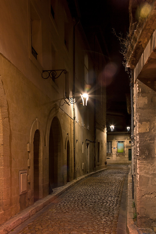 An atomospheric, narrow street seems spooky after dark, Avignon, France.