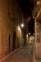 An atomospheric, narrow street seems spooky after dark, Avignon, France.