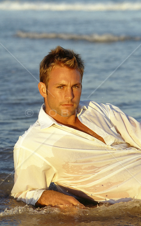portrait of a handsome man in the ocean at sunset
