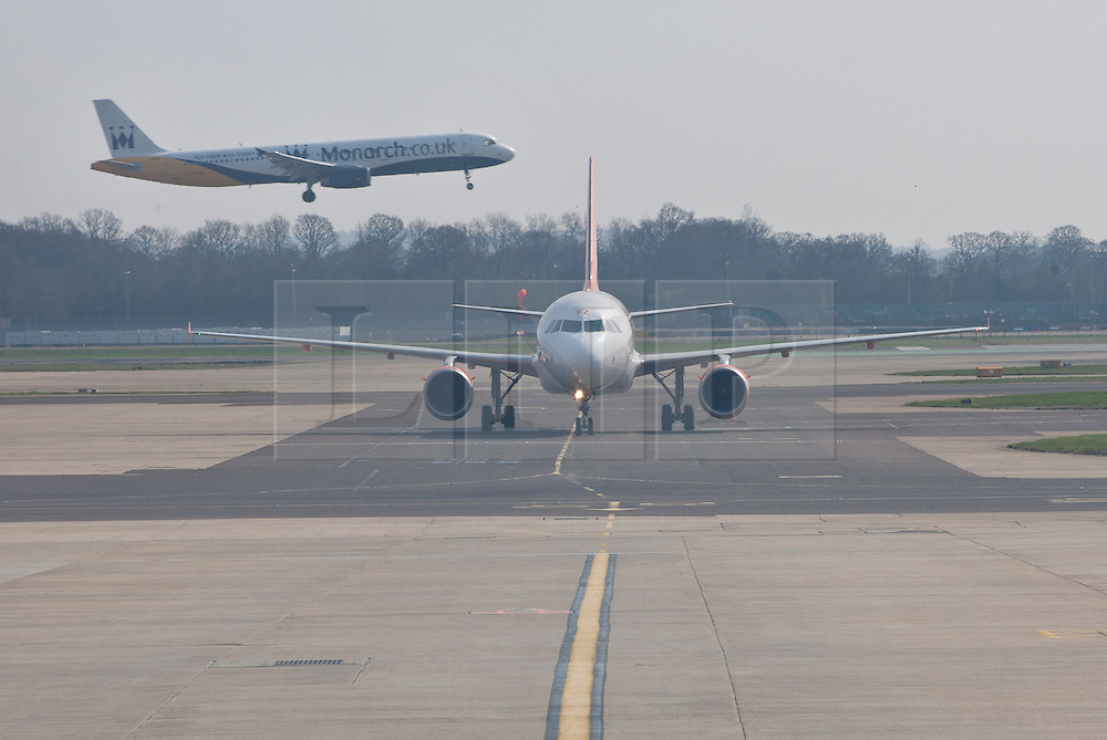 © licensed to London News Pictures. London, UK 23/03/2012. A Monarch Airlines plane landing as an EasyJet airplane preparing for take off at Gatwick Airport. Photo credit: Tolga Akmen/LNP