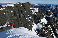 A lone climber ascends to the summit snowfield of Mt. Cain looking South towards Campbell River on central Vancouver Island.  British Columbia, Canada.