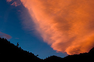 A lenticular cloud is colored orange at sunset in Clear Creek Canyon over the Rocky Mountains near Golden, CO