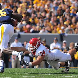 Oct 4, 2008; Morgantown, WV, USA; West Virginia quarterback Jarrett Brown (16) avoids the diving tackle of Rutgers linebacker Kevin Malast (34) during the third quarter of West Virginia's 24-17 victory over Rutgers at Milan Puskar Stadium.