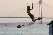 Boy jumping into sea, Howrah Bridge in background. Calcutta. India.