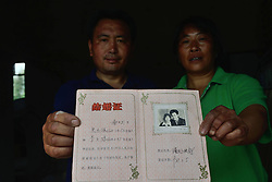 59601371 .The 47-year-old Zhu Zhiqiang (L) and his 47-year-old wife Li Ziqiong pose for photo with their marriage certificate in the quake-hit Longmen Village, southwest China s Sichuan Province, May 4, 2013. They took the photo for the certificate in 1989. Old photos are not daily necessities for who just suffered a 7-magnitude earthquake, but they are still cherished as they recorded peoples past life and recalled memories, May 4, 2013.  Photo by: i-Images.UK ONLY