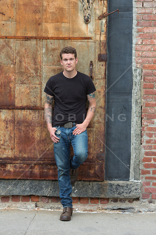 young man with tattoos  in a black tee shirt and jeans outdoors