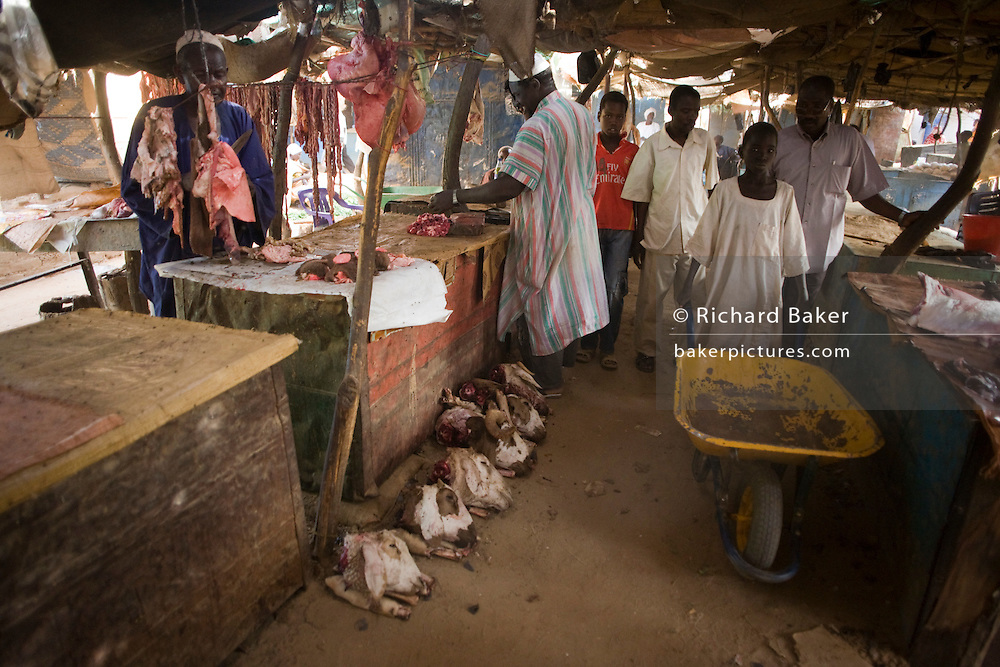 The heads of butchered goats lie in the dirt floor of the souk in the 4 sq km Abu Shouk refugee camp which is (disputedly) home to 38,000 displaced persons and families on the outskirts of the front-line town of Al Fasher (also spelled, Al-Fashir) in north Darfur.
