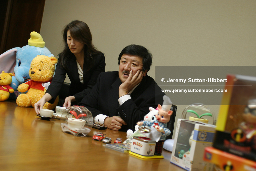 An employee brings a second cup of coffee for Kantaro Tomiyama, President and CEO, of 'TOMY Company Ltd. (a Japanese childrens toy manufacturing company), in Tokyo, Japan on Wednesday, Dec. 1st 2004. During interviews it is common for female assistants to enter the rooms silently , bringing refreshment drinks of green tea, coffee, or orange juice, to the company head and his guests.