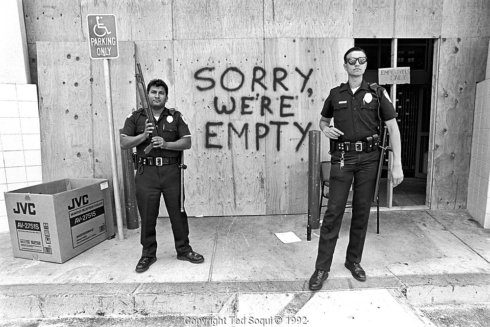 Two armed officers stand guard out front of an electronics store on Sunset Blvd. and La Brea Ave after being looted by rioters.<br /> <br /> 25 before and after LA92 photo project.