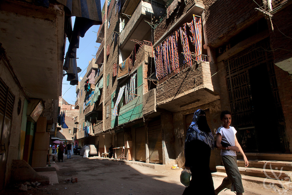An Egyptian boy escorts his mother down a residential street in the working class Cairo neighborhood of Imbaba, Egypt July 16, 2011. Crime, unemployment and inflation have continued to rise in post-revolutionary Egypt. (Photo by Scott Nelson)