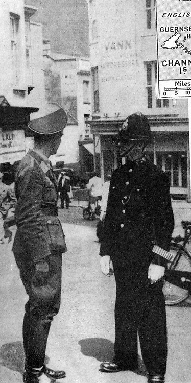 German army officer talking to a policeman in British  uniform, St Helier, Jersey.  The Channel Islands, part of Great Britain, were under German military occupation from 30 June 1940 to 9 May 1945.