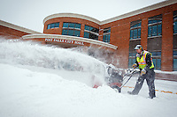 Bryan Myers clears snow from the driveway of the City Hall entrance Wednesday in Post Falls as the snow continues to fall.
