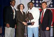 (L-R) Houston Oilers quarterback Warren Moon, a female NFL executive, 1990 NFL Man of the Year winner and Chicago Bears linebacker Mike Singletary, and NFL Properties President John Bello pose for a photo during the week of NFL Super Bowl XXV between the New York Giants and the Buffalo Bills on January 23, 1991 in Tampa, Florida. ©Paul Anthony Spinelli