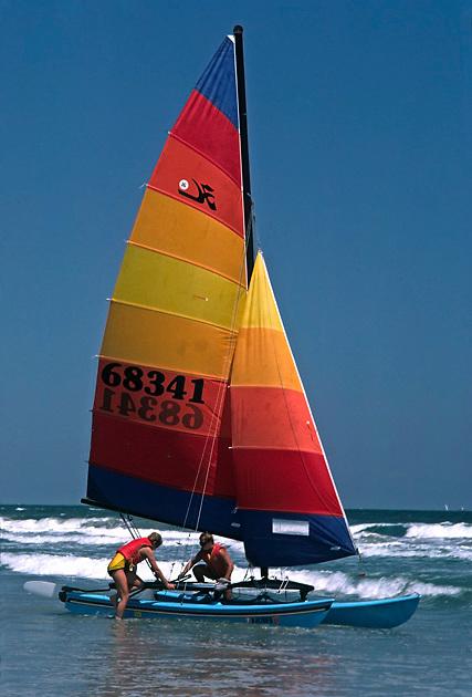 2 men board small catamaran sailboat in ocean surf; colorful sail; 16' Hobie Cat; sport; recreation; challenge; Atlantic Ocean; New Jersey shore