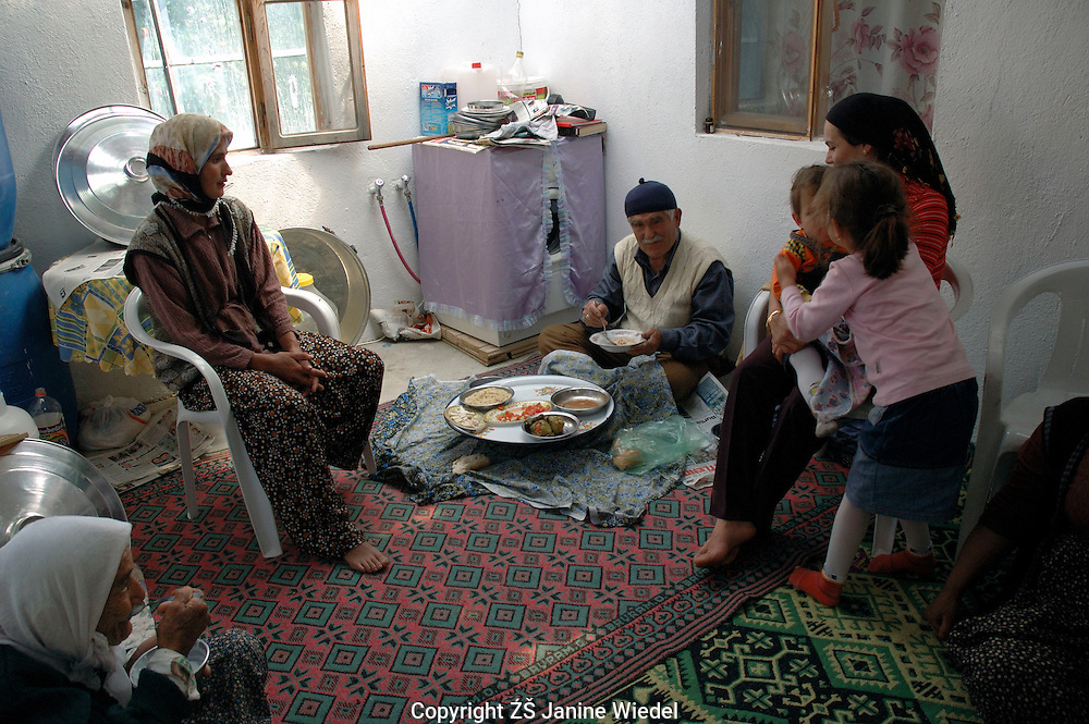 Extended Turkish family having midday meal in their home in small rural village in Southern Turkey.