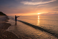 A fisherman casts his line out into Lake Superior at sunset