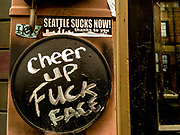 """Cheer Up Fuck Face"" graffitied on a wall next to a sticker that says ""Seattle Suck Now! Thanks to you."""
