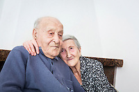 ACCIAROLI (POLLICA), ITALY - 5 OCTOBER 2016: (R-L) 93-years-old Amina Fedullo hugs her 100-years-old husband Antonio Vassallo in their home in Acciaroli, a hamlet in the municipality of Pollica, Italy, on October 5th 2016. Mrs Fedullo was a farmer her entire life, while Mr Vassallo was a soldier in Italy's military forces in the Italian East Africa, the Italian colony in the Horn of Africa. They've been married for 66 years.<br /> <br /> To understand how people can live longer throughout the world, researchers at University of California, San Diego School of Medicine have teamed up with colleagues at University of Rome La Sapienza to study a group of 300 citizens, all over 100 years old, living in Acciaroli (Pollica), a remote Italian village nestled between the ocean and mountains in Cilento, southern Italy.<br /> <br /> About 1-in-60 of the area's inhabitants are older than 90, according to the researchers. Such a concentration rivals that of other so-called blue zones, like Sardinia and Okinawa, which have unusually large percentages of very old people. In the 2010 census, about 1-in-163 Americans were 90 or older.