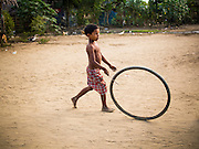 05 NOVEMBER 2014 - SITTWE, RAKHINE, MYANMAR: A Rohingya Muslim boy plays with a tire in a Rohingya Muslim IDP camp near Sittwe. After sectarian violence devastated Rohingya communities and left hundreds of Rohingya dead in 2012, the government of Myanmar forced more than 140,000 Rohingya Muslims who used to live in and around Sittwe, Myanmar, into squalid Internal Displaced Persons camps. The government says the Rohingya are not Burmese citizens, that they are illegal immigrants from Bangladesh. The Bangladesh government says the Rohingya are Burmese and the Rohingya insist that they have lived in Burma for generations. The camps are about 20 minutes from Sittwe but the Rohingya who live in the camps are not allowed to leave without government permission. They are not allowed to work outside the camps, they are not allowed to go to Sittwe to use the hospital, go to school or do business. The camps have no electricity. Water is delivered through community wells. There are small schools funded by NOGs in the camps and a few private clinics but medical care is costly and not reliable.   PHOTO BY JACK KURTZ