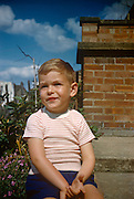 A young boy of about 5 years-old sits in the family back garden in the early 1960s. The small lad sits with an embarrassed expression on his face, a brick wall behind him with summer garden plants growing nearby. The boy has blonde hair and a striped t-shirt and was recorded on a film camera by the boy's father, an amateur photographer in 1964. The picture shows us a memory of nostalgia in an era from the last century.