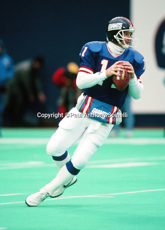 New York Giants quarterback Phil Simms (11) drops back to pass during the NFL football game against the Houston Oilers on Dec. 21, 1991 in East Rutherford, N.J. The Giants won the game 24-20. (©Paul Anthony Spinelli)
