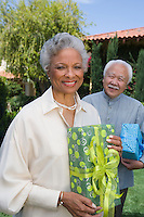 Senior man and woman holding birthday presents, smiling