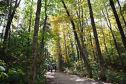 New Hampshire: A couple walks along the Sabbaday Brook trail off the Kancamagus Highway at the beginning of Autumn.