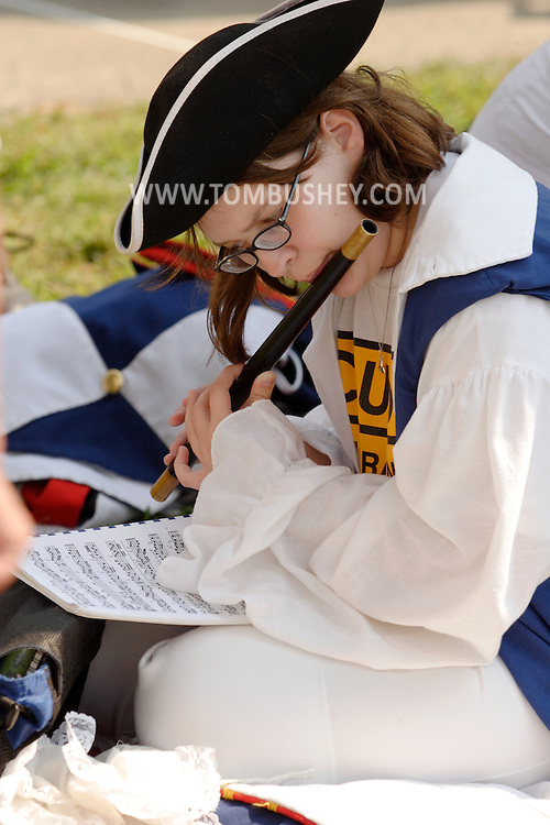 Middletown, N.Y. - A member of the Coldenham Pipe and Drum Corps practices playing her fife before marching in the Middletown Fire Department's 147th Anniversary Fire Parade on Sept. 9, 2006. ©Tom Bushey