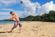 A traveler does some tropical baseball with coconut and stick at Wizard Beach in Bocas del Toro, Panama