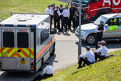 London, UK. 19th April, 2019. A group of senior police officers meets alongside the main motorway approach to Heathrow airport following a small protest earlier by Extinction Rebellion Youth. A large police presence is evident around the airport but so far any disruption feared by the airport authorities from Extinction Rebellion climate change activists has been symbolic rather than material. Credit: Mark Kerrison/Alamy Live News