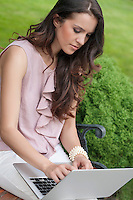 Beautiful young woman using laptop on bench in park
