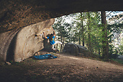 Climber jumping legs in a overhanging rock boulder in the middle of the forest