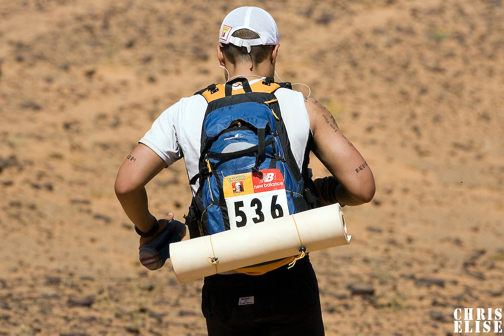 30 March 2007: #536 Jerry Pi of USA runs in erg Znaigui en route to check point 3 during fifth stage of the 22nd Marathon des Sables between west of Kfiroun and erg Chebbi (26.22 miles). The Marathon des Sables is a 6 days and 151 miles endurance race with food self sufficiency across the Sahara Desert in Morocco. Each participant must carry his, or her, own backpack containing food, sleeping gear and other material.