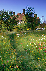 Grass path through the meadow at Great Dixter, East Sussex. The house designed by Edwin Lutyens in the distance