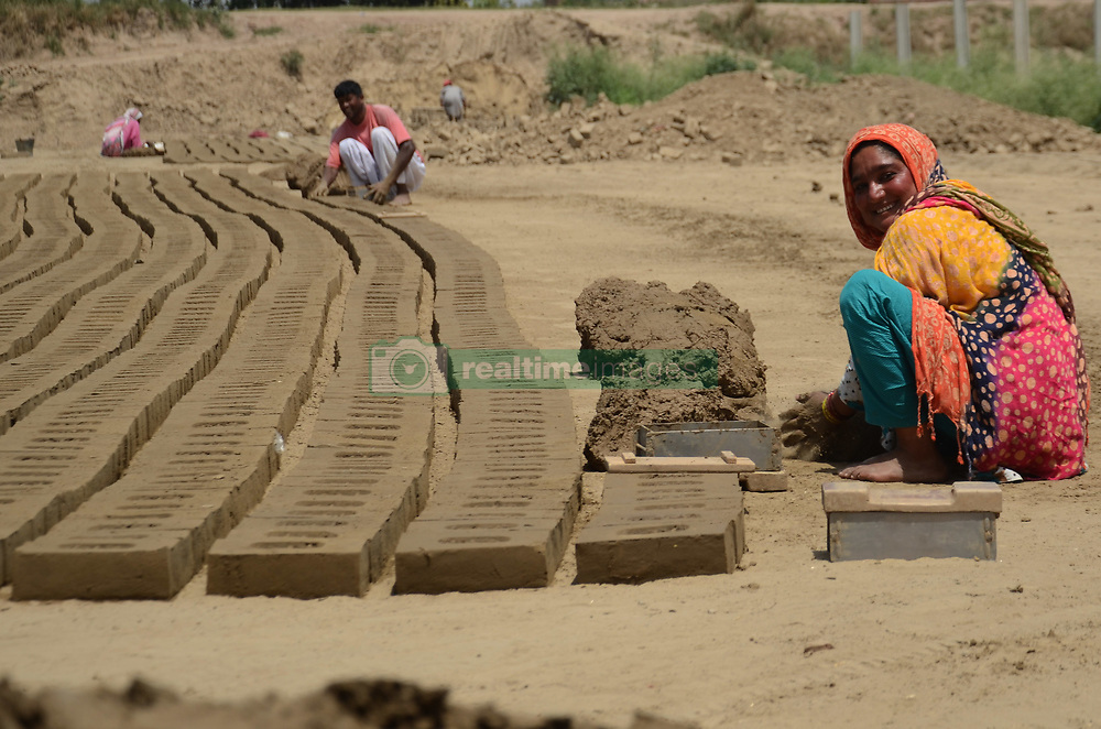 "April 30, 2019 - Lahore, Punjab, Pakistan - Pakistani villagers women and family members laborers are busy in preparing of clay tiles at a bricks klin on the eve of International Labour Day Lahore . May 1st, International Workers Day, commemorates the historic struggle of working people throughout the world. The 1904 International Socialist Conference in Amsterdam, the Sixth Conference of the Second International, called on All Social Democratic Party Organizations and Trade Unions of All Countries to demonstrate energetically on the first of May for the legal establishment of the 8-hour day, for the class demands of the proletariat, and for universal. celebrates all over the global to pay tribute to those who laid down their lives in Chicago in 1886 for the rights of laborers with the theme of Uniting Workers for Social and Economic Advancement. It was in 1972 when Pakistan,s first labor policy was devised and May 1st was officially declared as a holiday. Pakistan,s labor constitutes without doubt the most miserable community in the country. Labor Day is an annual holiday celebrated all over the world on May 01"" that resulted from efforts of the labor union movement, to celebrate the economic and social achievements of workers. The holiday was organized by the Central Labor Union to exhibit ''the strength and esprit de corps of the trade and labor. International Workers' Day, also known as Labor Day or Workers' Day in some countries and often referred to as May Day, is a celebration of laborers and the working classes that is promoted by the international labor movement which occurs every year on May Day  (Credit Image: © Rana Sajid Hussain/Pacific Press via ZUMA Wire)"