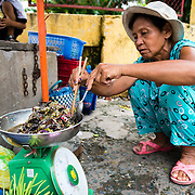 Woman preparing food at street stall in a market in Saigon