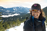 Deanna enjoys a smile and a rest after snowshoeing up a mountain with a view of Whistler and Blackcomb Mountains.
