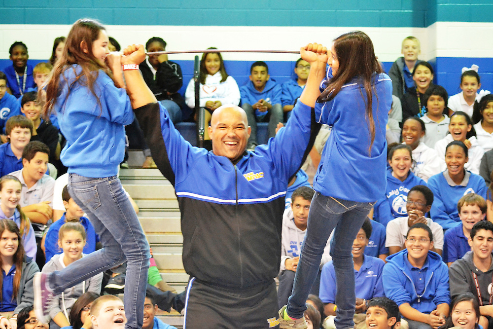 """Stephen Mackey of """"Team Impact""""—a group that encourages kids to work hard and believe in themselves through displays of strength—lifts Pin Oak Middle School students Madeline Ashcroft and Noor Malik using a makeshift barbell. During their shows, Mackey and his team of 19 use their strength to rip phone books in half, break wooden bats over their knees and bend iron rods into neat little ties.<br /> To submit photos for inclusion in eNews, send them to hisdphotos@yahoo.com."""